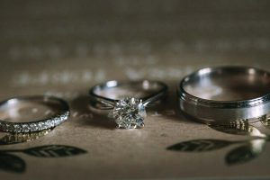 a green wedding with gold accents in new brunswick - wedding rings