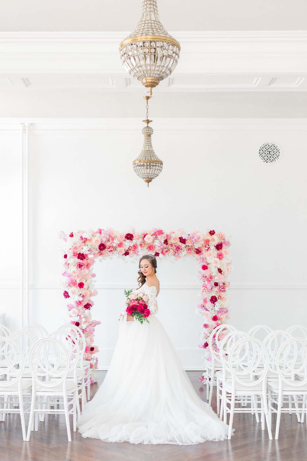 The Prettiest Romantic Pink Wedding Inspiration - bride in front of ceremony arch