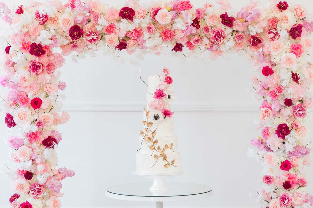 The Prettiest Romantic Pink Wedding Inspiration - cake in front of ceremony arch