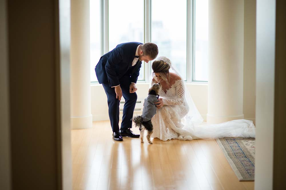 A Classic Vintage inspired Wedding at the One King West in Toronto - Bride and Groom Embracing Dog