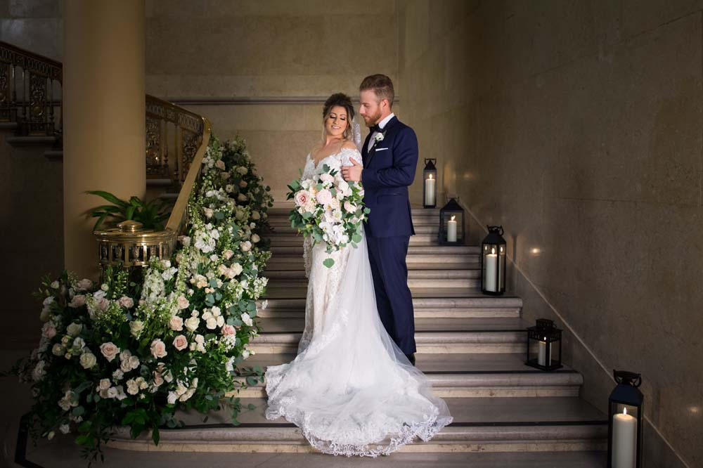 A Classic Vintage inspired Wedding at the One King West in Toronto - Bride and Groom on Floral Staircase