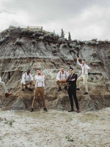 Groomsmen posing in front of a sand dune